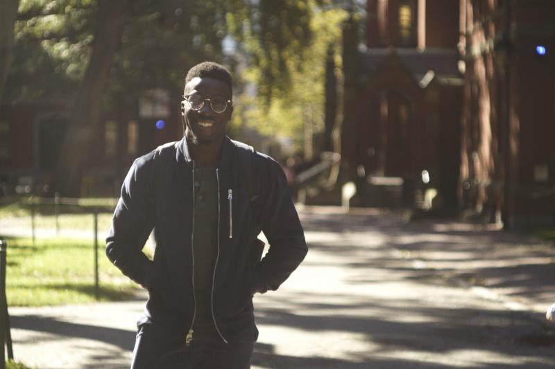 Student smiling and walking through Harvard Yard