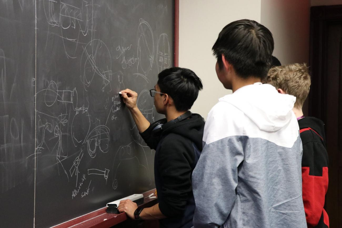 students working on a problem on a chalkboard
