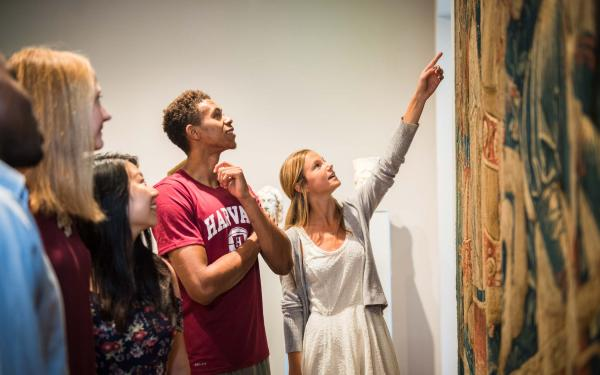 Students examining a piece in the art museums