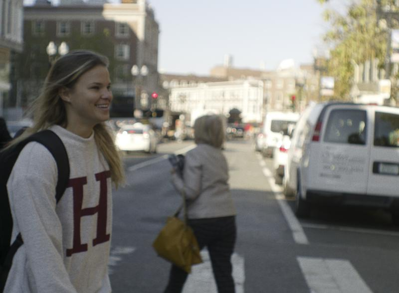 Student wearing Harvard sweatshirt walking towards Harvard Yard